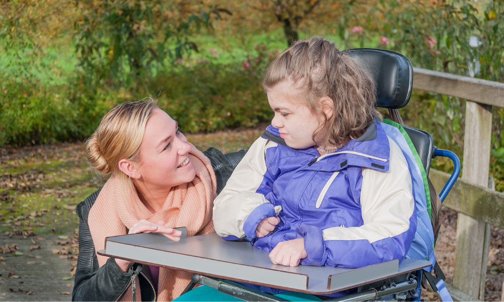 woman talking to child in wheelchair